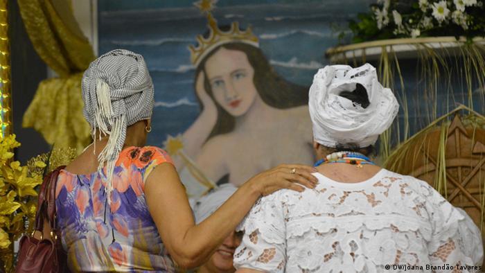 Duas mulheres contemplam imagem de Iemanjá
