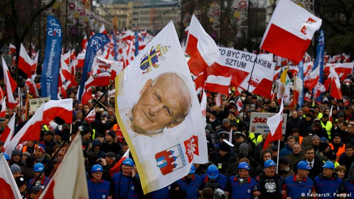 A huge flag of Pope John Paul II billows over a crowd of pro-government supporters dressed in blue and carrying red and white flags