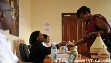 Bildunterschrift:A poll clerk hands gives ballot papers to a registered Rwandan voter at a polling station on December 17, 2015 at the Rwandan High Commission in Nairobi. Rwandans abroad were voting on Thursday in a referendum to amend the constitution allowing President Paul Kagame to rule until 2034, a day ahead of the main vote inside the country. The constitutional amendment -- passed by parliament last month -- reduces presidential terms to five years and maintains a two-term limit, but makes an exception for Kagame. / AFP / TONY KARUMBA (Photo credit should read TONY KARUMBA/AFP/Getty Images)