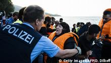 A German police officer, representative of the EU's border management agency Frontex, helps refugees and migrants arriving on the Greek island of Lesbos after crossing the Aegean Sea from Turkey, on October 17, 2015. Twelve migrants drowned when their boat sank off the Turkish coast as they were seeking to reach Greece, while around 25 others were rescued, the Anatolia news agency reported. AFP PHOTO / DIMITAR DILKOFF (Photo credit should read DIMITAR DILKOFF/AFP/Getty Images)