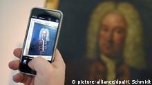 04.03.2015 *** ARCHIV - ILLUSTRATION - Ein Porträt, das mit höchster Wahrscheinlichkeit Georg Friedrich Händel zeigt, fotografiert ein Besucher am 04.03.2015 mit seinem Smartphone in der Ausstellung des Händel-Hauses in Halle (Saale) (Sachsen-Anhalt). Im Louvre drängeln sich täglich Hunderte Besucher, um die Mona Lisa mit dem Smartphone zu fotografieren. Wer in deutschen Museen den Fotoapparat oder das Handy zückt, bekommt es mit dem strengen Aufsichtspersonal zu tun. Die CDU-Opposition im nordrhein-westfälischen Landtag fordert nun in einem Antrag, dass Museen sich stärker den kommunikativen Gewohnheiten ihrer Besucher anpassen, «wenn sie nicht an Relevanz verlieren wollen». Foto: Hendrik Schmidt/dpa +++(c) dpa - Bildfunk+++ Copyright: picture-alliance/dpa/H. Schmidt