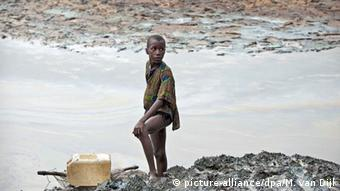 A boy on an oil-stained river bank in Ogoniland