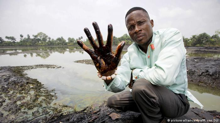 A man showing his hand dirty with oil after plunging it in the Niger Delta