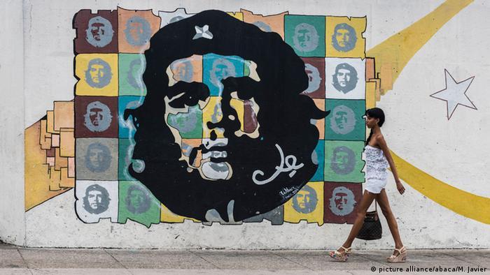 Eine Frau geht in Havanna an einem großen Graffiti des Gesichts von Che Guevara vorbei (Foto: Picture Alilance)