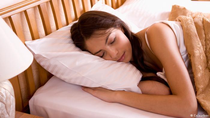 Mujer durmiendo con el brazo debajo de una almohada (Colourbox)