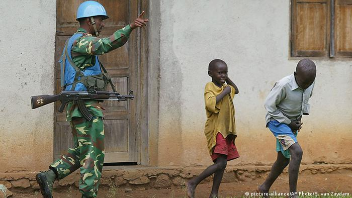 Warrant Officer Mosharrof from Bangladesh, asks children to move away from the area he is patrolling in the small village of Boga near Bunia, Democratic Republic of Congo, on in this Saturday, April 24, 2004 AP Photo/Schalk van Zuydam