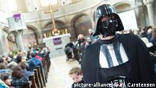 Ein Mann hat sich als Darth Vader für den Star-Wars-Gottesdienst am 20.12.2015 in der Zionskirche in Berlin entsprechend verkleidet. Foto: picture-alliance/dpa/J. Carstensen