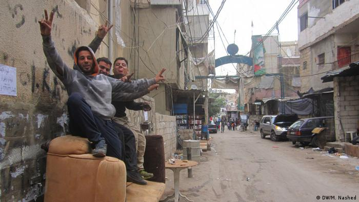 Three men in Shatila take a break from construction work.