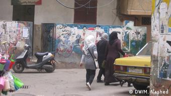 Loose electricty wires dangle over the heads of women walking through Shatila camp.