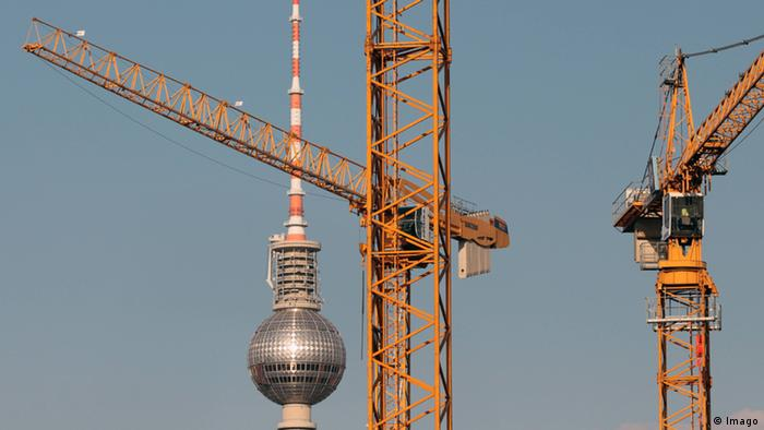 Construction cranes in front of the Berlin television tower.