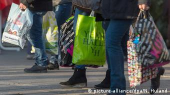 Ноги покупателей, несущих многочисленные покупки