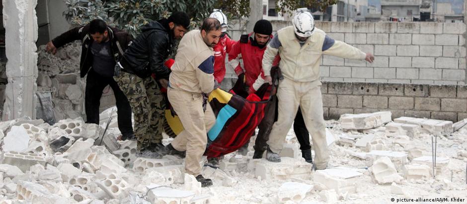 Ferido é carregado após ataque aéreo russo em área residencial em Jisr al-Sughur, na Síria, em 18 de dezembro