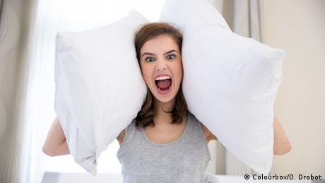 Eine ärgerliche Frau hält sich mit zwei Kissen die Ohren zu (Colourbox/D. Drobot)