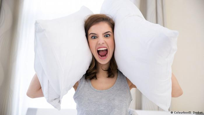 Woman with pillows over her ears