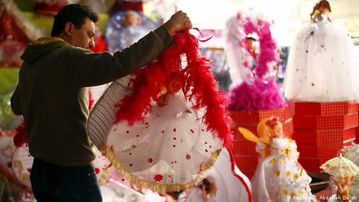 A man shops for traditional bride of Moulid dolls at a street market