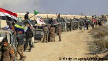 December 22, 2015 Bildunterschrift:Iraqi pro-government forces stand next to armored vehicles as they take position in al-Aramil area, south of the Anbar province's capital Ramadi, during military operations on December 22, 2015. Iraqi security forces advanced into the centre of the city for a final push aimed at retaking the city they lost to the Islamic State jihadist group in May 2015. Getty Images/AFP/Stringer