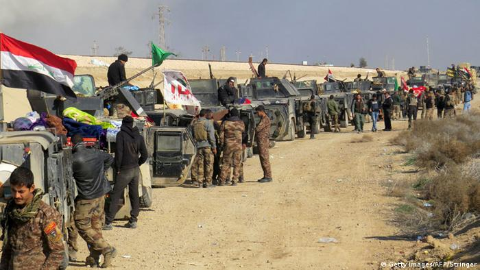 Iraqi pro-government forces stand next to armored vehicles as they take position in al-Aramil area, south of the Anbar province's capital Ramadi, during military operations on December 22, 2015 (Photo: Getty Images/AFP/Stringer)