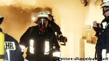 Feuerwehrleute arbeiten am 23.12.2015 in Wallerstein (Bayern) bei einem Brand bei einem Wohnhaus. Bei Brandanschlägen auf zwei benachbarte Wohnhäuser sind zwölf Menschen verletzt worden. Einen ausländerfeindlichen Hintergrund schlossen die Ermittler nicht aus. Foto: Dieter Mack/dpa +++(c) dpa - Bildfunk+++