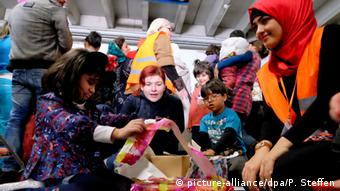 Children in an emergency refugee shelter in Germany unpack Christmas gifts