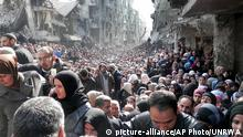 FILE - This picture taken on Jan. 31, 2014, and released by the United Nations Relief and Works Agency for Palestine Refugees (UNRWA), shows residents of the besieged Palestinian camp of Yarmouk, queuing to receive food supplies, in Damascus, Syria. From the three-year-old boy who washed ashore on a Turkish beach to the 71 migrants who suffocated in a truck in Austria to the daily scenes of chaos unfolding in European cities as governments try to halt a human tide heading north. There is no let up to the horrors that Syria¿s civil war keeps producing. Syria¿s brutal conflict, now in its fifth year, has touched off the greatest humanitarian crisis of our time. About 250,000 people have been killed and more than one million wounded since March 2011, according to U.N. officials. (UNRWA via AP, File) picture-alliance/AP Photo/UNRWA