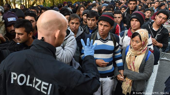 German police officer stood with refugees at Austrian border