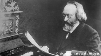 Max Bruch sits at a piano reading a score in a black and white photo from around 1905