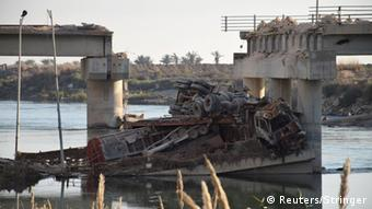 A burned out tractor trailor lies atop a collapsed bridge span over a river in Ramadi.