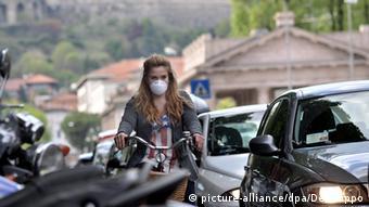 Велосипедистка в Милане в маске из-за смога
