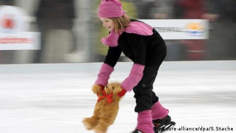Ein Mädchen läuft Schlittschuh und zieht dabei einen Teddy mit übers Eis (picture-alliance/dpa/S.Stache)