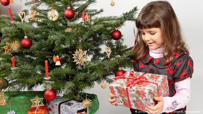 A girl with a present next to a Christmas tree (Photo: picture alliance/chromorange/E. Weingartner)