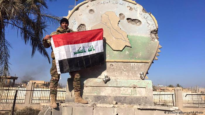 An Iraqi soldier holds a national flag in the government complex in central Ramadi, 70 miles west of Baghdad, Iraq, after military forces retook the city from Islamic State militants