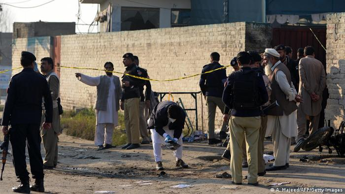 Pakistani security personnel collect evidence at the bomb blast site in Mardan