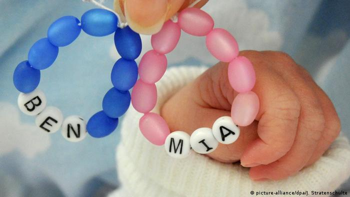 Baby hand with bracelets with names Ben and Mia (picture-alliance/dpa/J. Stratenschulte)