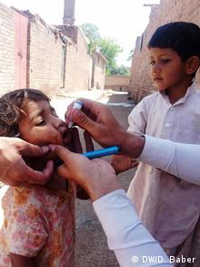 A Pakistani health worker vaccinates a child aginst polio with drops.