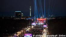Lichstrahlen ragen am 31.12.2015 in Berlin auf der Straße des 17. Juni am Brandenburger Tor hinauf in den dunklen Abendhimmel. Dort findet die Silvesterparty statt. picture-alliance/dpa/P. Zinken