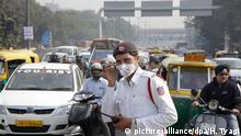 epa05085046 A traffic police man stands at traffic lights wearing a pollution mask during the first day of the implementation of the odd-even scheme for the vehicles in New Delhi, India, 01 January 2016. Authorities in New Delhi launched a plan to limit the number cars on the roads to tackle alarming levels of pollution in the city. Under the 15-day trial initiative, private cars are being allowed on the roads on alternate days depending on whether their number plate ends with with an odd or even number. The restrictions will be implemented from 8 am to 8 pm on all days except Sunday. Violators will be fined 2,000 rupees (30 US dollar). The Indian capital, with an estimated population of 17 million, was the most polluted city in the world in 2014 according to the World Health Organization (WHO). EPA/HARISH TYAGI +++(c) dpa - Bildfunk+++