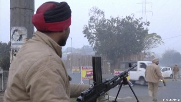 A policeman stands guard with a gun as vehicles pass by, following an attack on an Indian Air Force base in Pathankot on Saturday, near the border with Pakistan, in Ludhiana, Punjab state, India, in this still frame taken from video, January 2, 2016