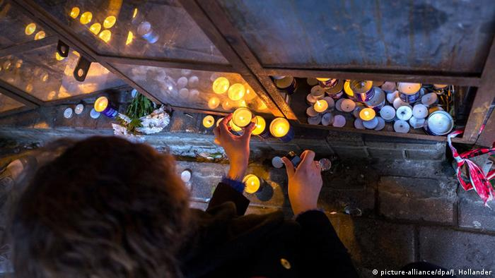 An Israeli woman lights a candle at a memorial in the entrance of the cafe in Tel Aviv, Israel.