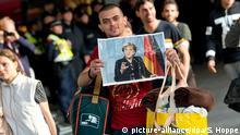 ARCHIV - Ein Flüchtling, der kurz zuvor mit einem Zug angekommen ist, läuft am 05.09.2015 auf dem Hauptbahnhof in München (Bayern) über den Bahnsteig und hält dabei ein Foto von Angela Merkel in den Händen. Foto: Sven Hoppe/dpa (zu: Etappen der Flüchtlingskrise) +++(c) dpa - Bildfunk+++ picture-alliance/dpa/S. Hoppe