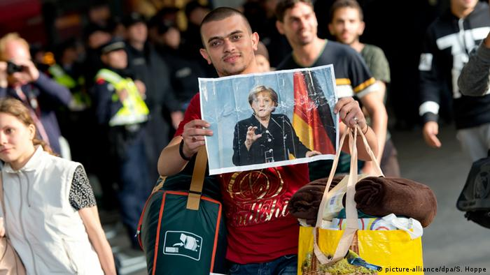 Беженцы с фотографиями Меркель на вокзале в Мюнхене