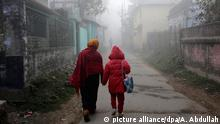 epa05087258 A woman walks in the streets with her daughter after the earthquake at Pabna, Bangladesh 04 January 2016. At least one man died and several injured after got panicked following a 6.8 magnitude earthquake hit across the country. The earthquake hit at 04:35 local time (23:05 GMT Sunday) about 33km (20 miles) northwest of Imphal, the capital of Manipur state, in northeast India, near its border with Myanmar and Bangladesh, according to the US Geological Survey (USGS). EPA/ABIR ABDULLAH