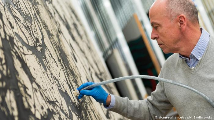 Otto Hubacek cleans Jackson Pollock's Number 32 - Copyright: picture-alliance/dpa/M. Skolimowska