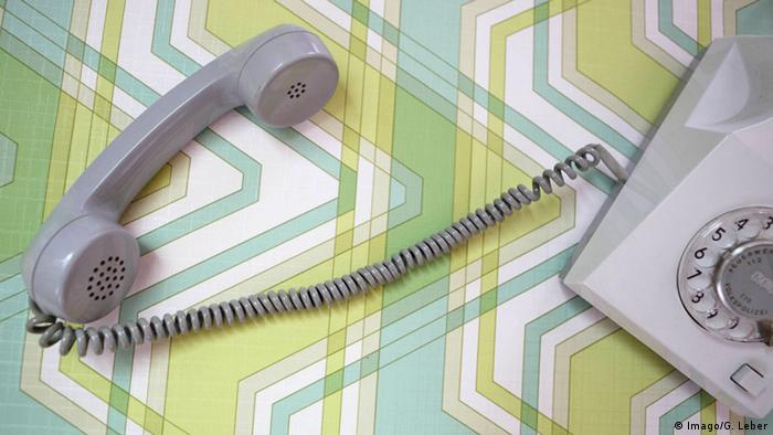 An old telephone on a green and blue patterened background