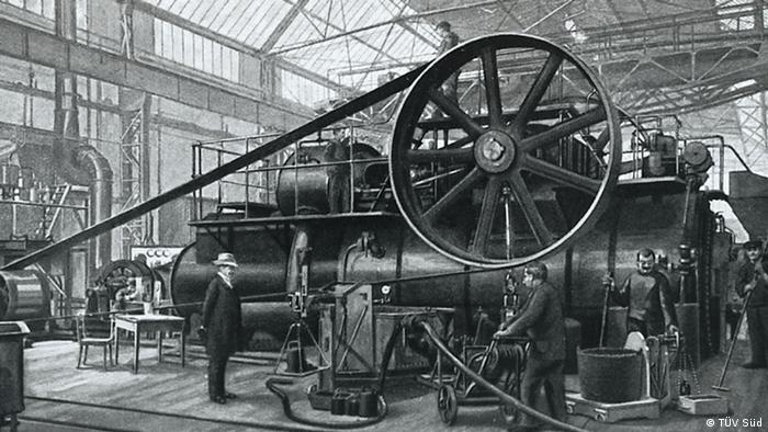 Bild einer alten Dampfmaschine, neben der Männer stehe