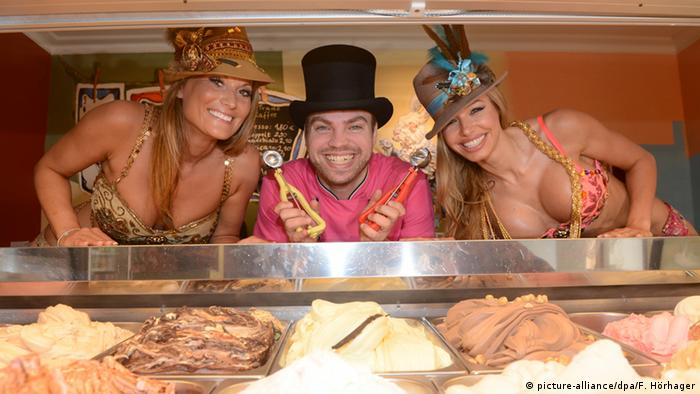 Matthias Münz Der verrückte Eismacher in his parlor, flanked by two women in bikinis. (picture-alliance/dpa/F. Hörhager)