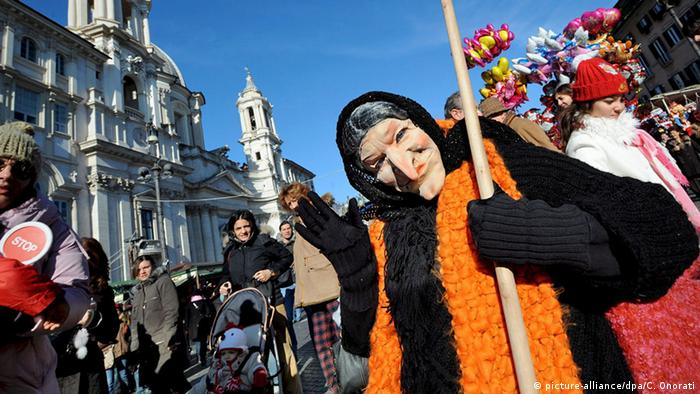 A person dressed as an old witch-like ady Befana waves at the camera in Rome