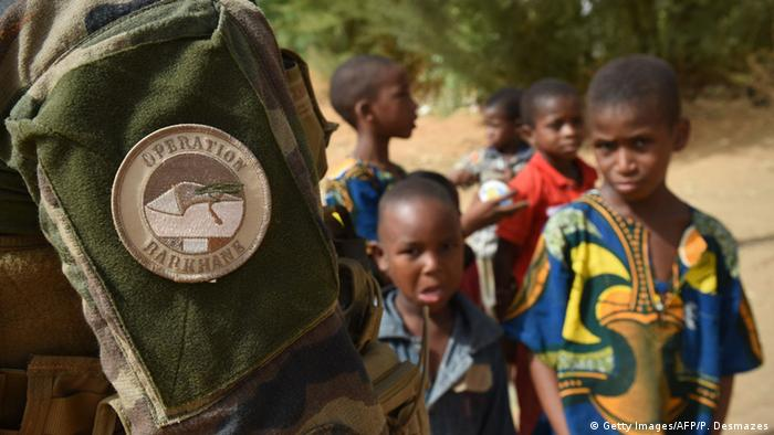 Des jeunes enfants se tiennent à côté d'un soldat français de l'opération Barkhane (Archives - Gao, 30.05.2015)