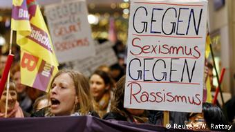 A woman holds a sign at a demonstration in Cologne, January 5