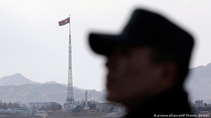 A South Korean soldier stands as North Korea's flag can be seen in the distance.