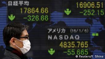 Японец с маской от гриппа на фоне табло с падающими биржевыми индексами